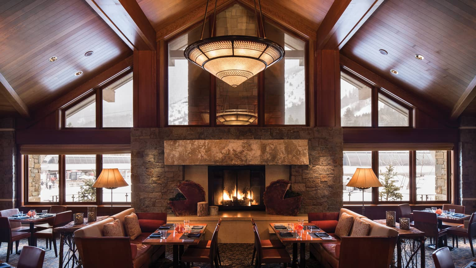 Westbank Grill tall cathedral ceilings, skylight windows over stone fireplace, dining tables, chairs