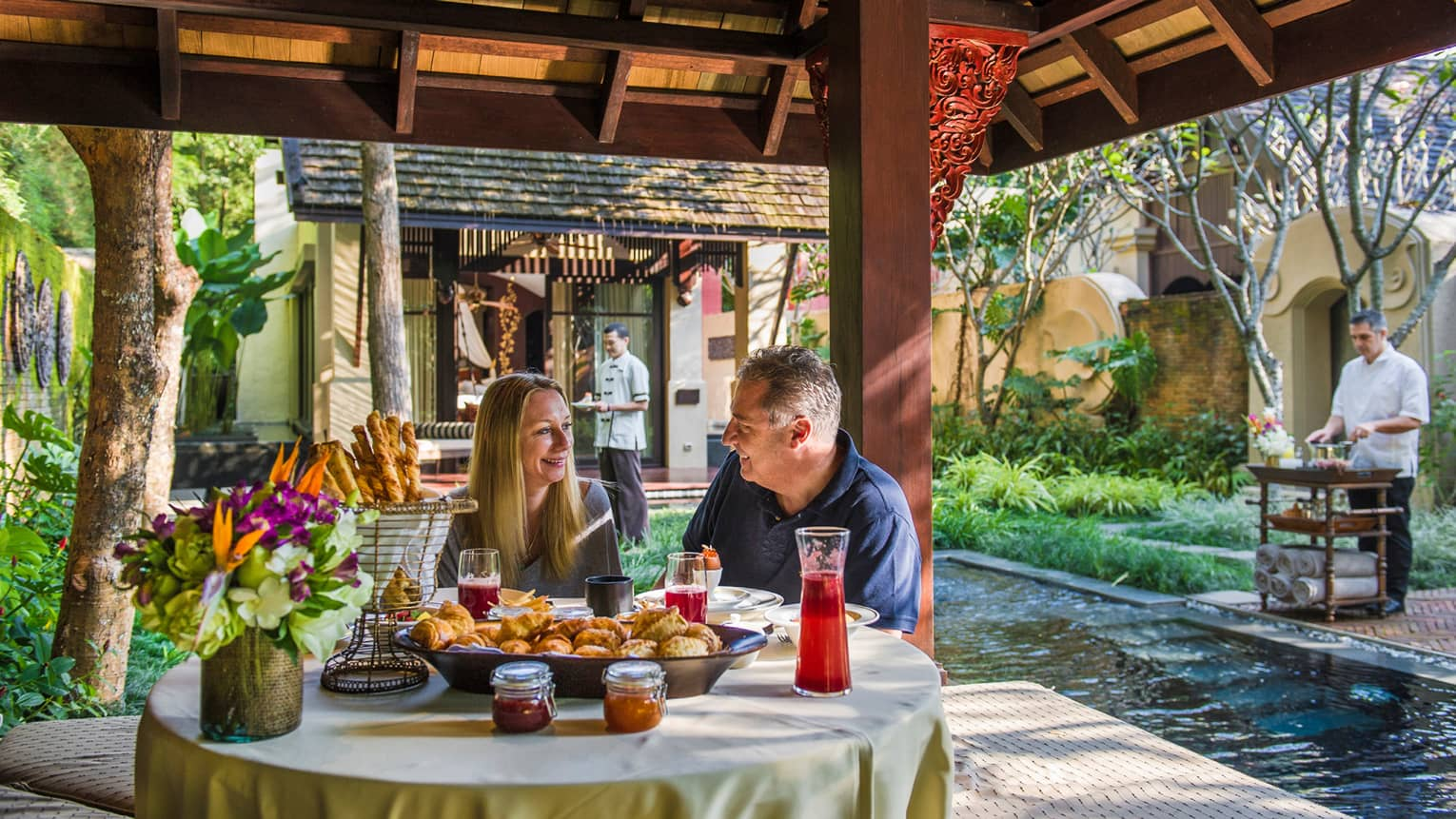 Smiling man and woman dine at table with baskets of pastries, breadsticks under wood gazebo