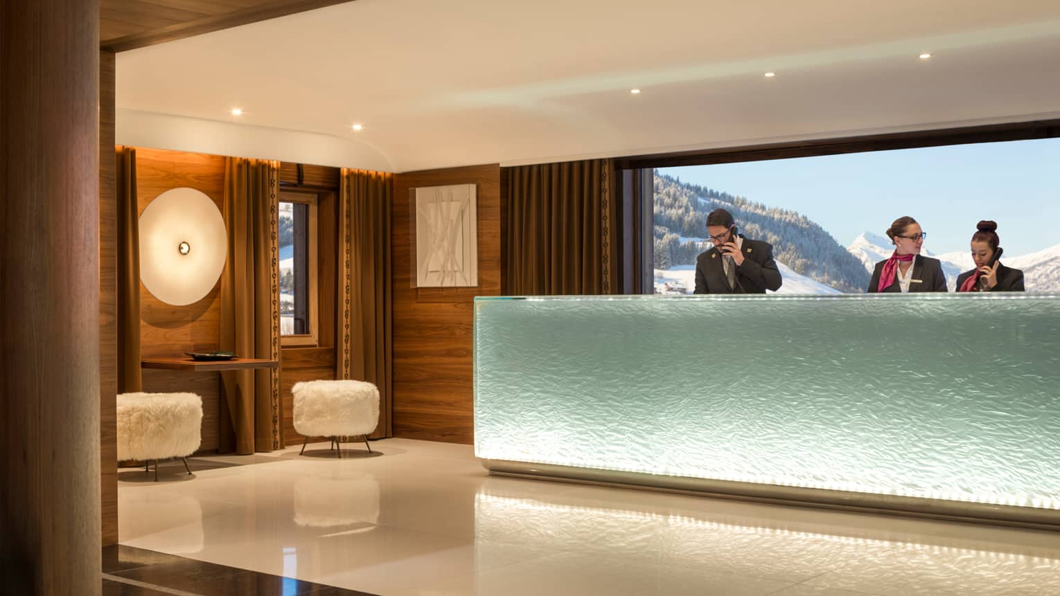 Hotel staff answer phones at frosted glass reception desk in modern lobby