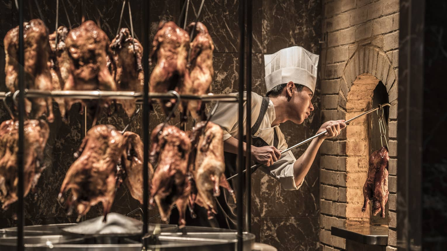 Rotisserie with hanging whole ducks in front of chef wearing white hat, taking duck from brick oven