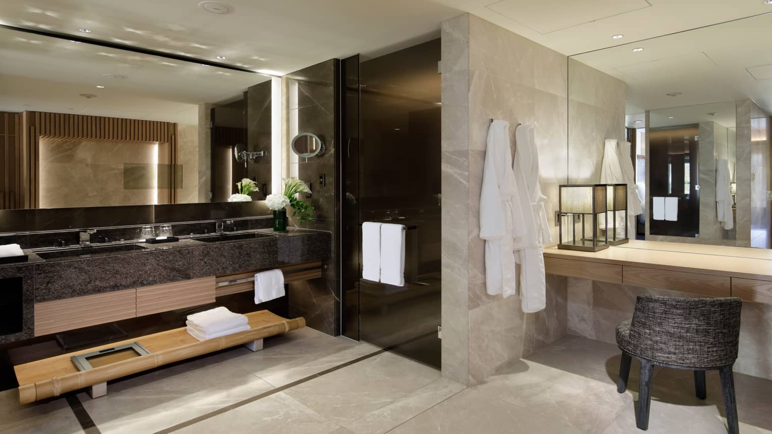 Large marble bathroom with double sink by black glass walk-in shower, vanity and chair