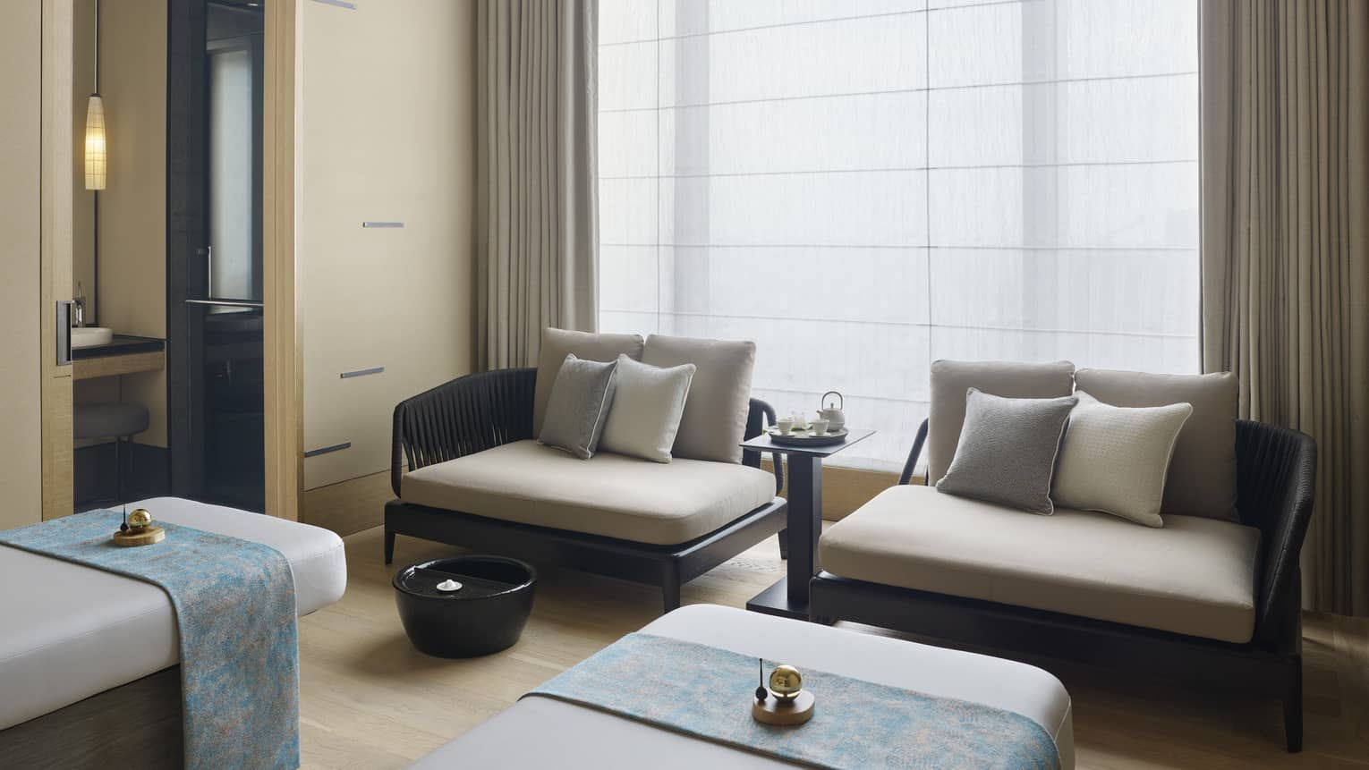 Couples Treatment Room, two spa treatment beds and small sofas under tall window