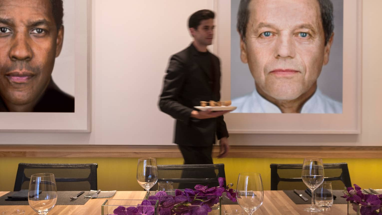 Server carries tray past Cut table, framed prints of Hollywood stars