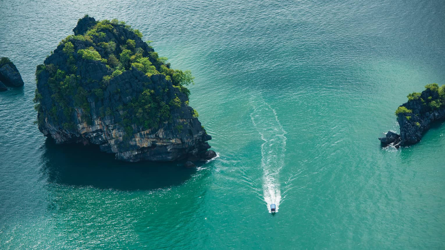 Ariel view of a boat driving through rock structures on emerald green water