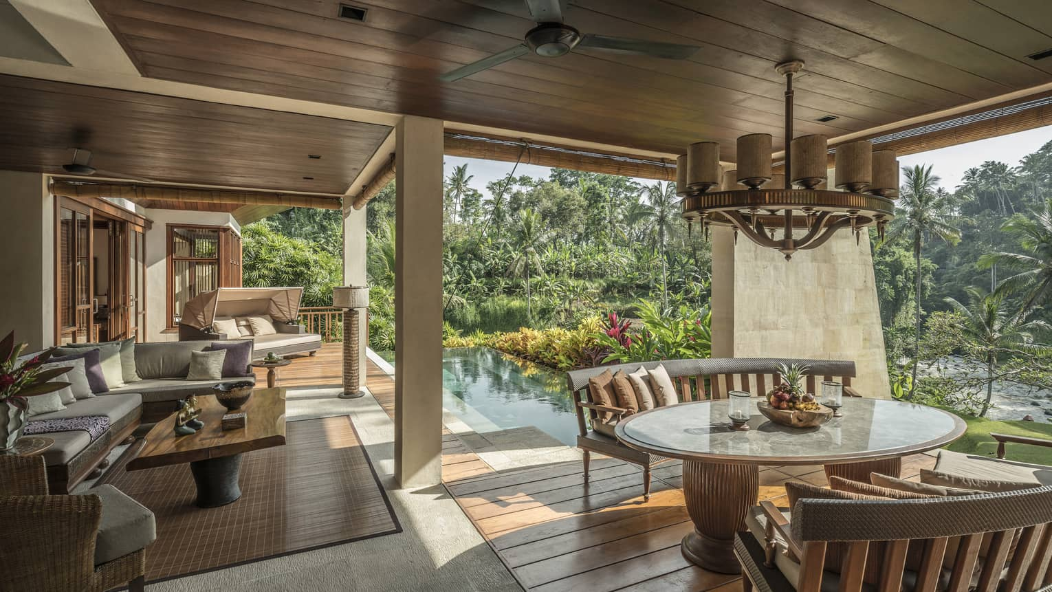 A villa with an outdoor patio and an infinity pool overlooking a river in Bali