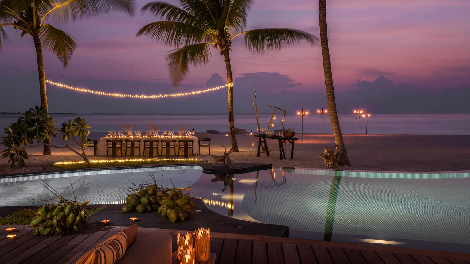 String of lights between palm tree over private dining table on beach by swimming pool at sunset