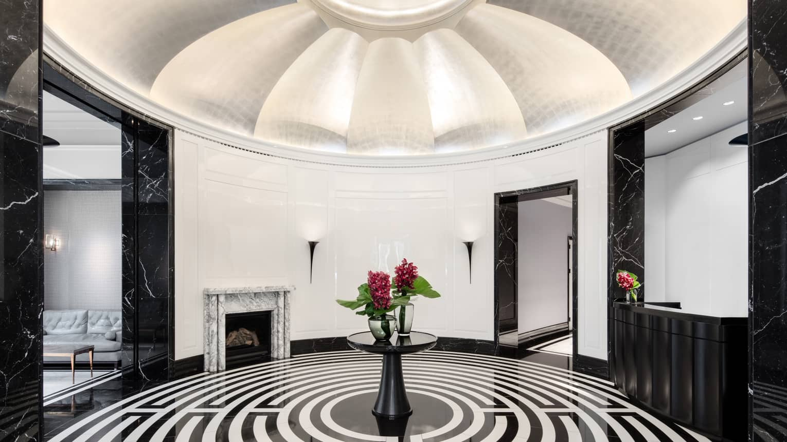 Dramatic white dome ceiling over rotunda with black-and-white maze flooring, red flowers on table