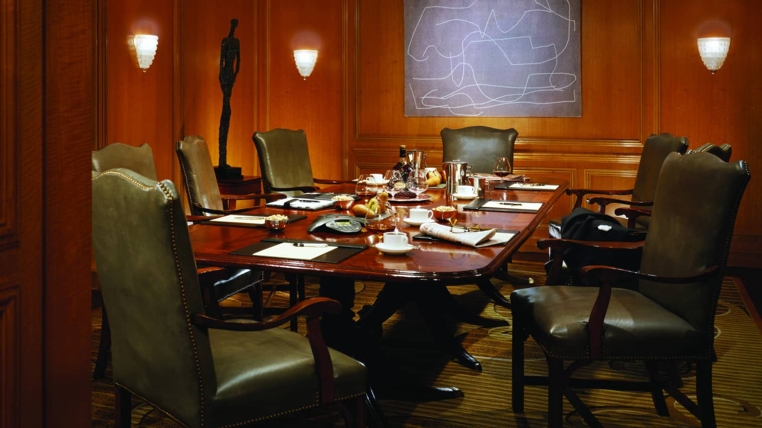 Large boardroom meeting table in room with wood panel walls