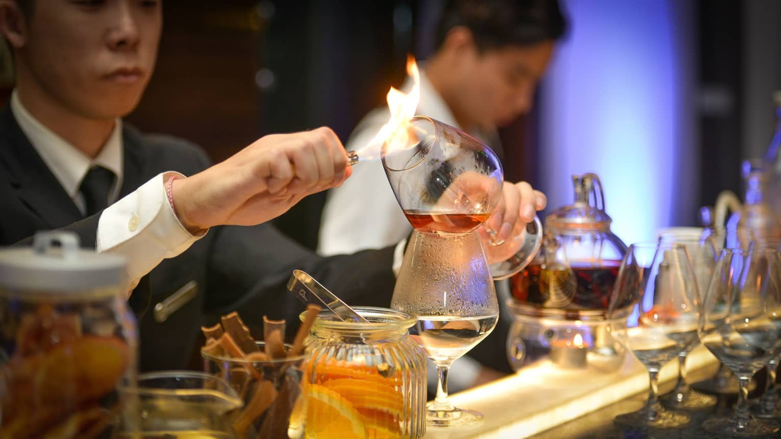 Opus Bar bartender holds flame to glass of liquor, prepares to pour it into cup