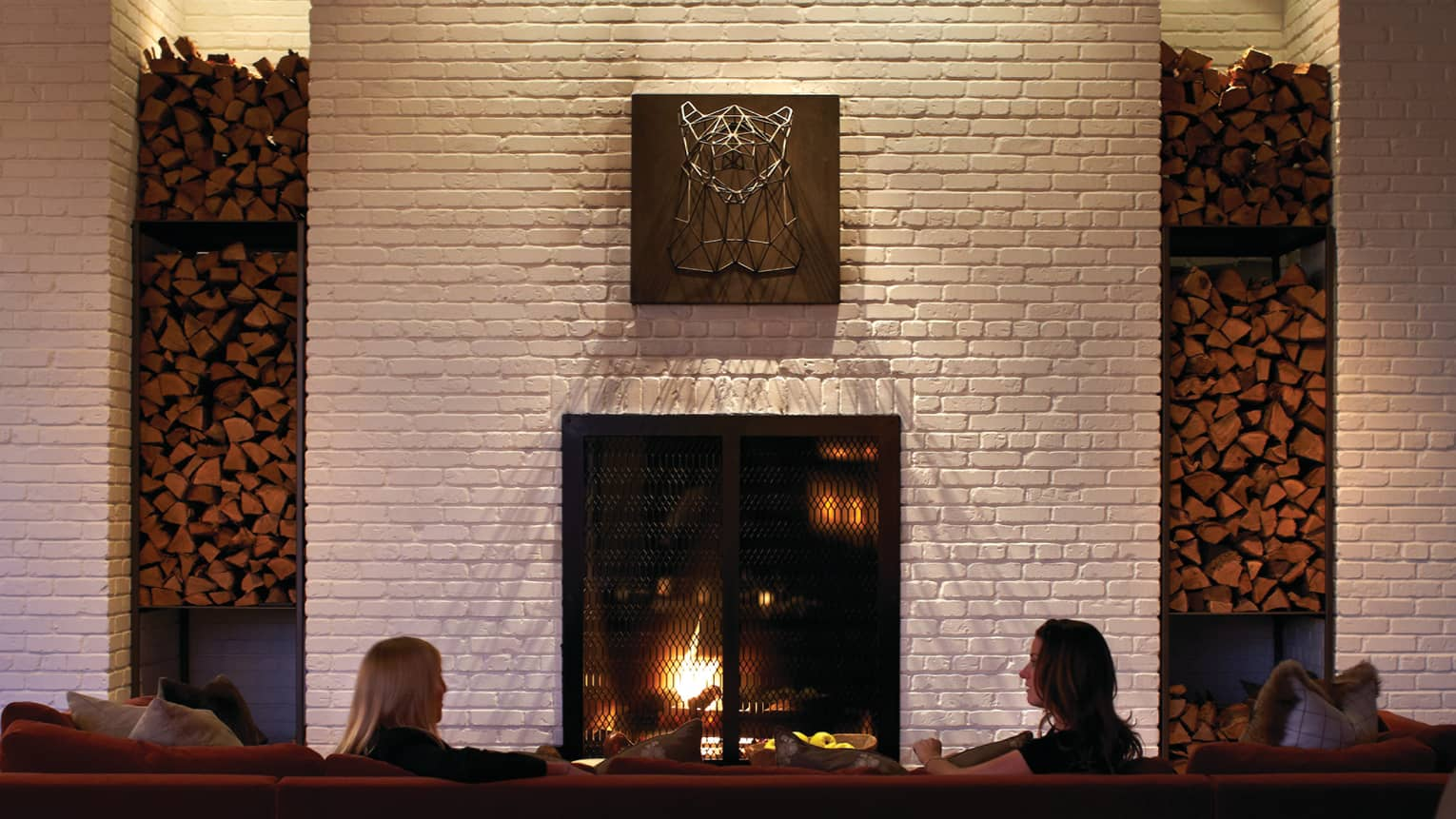 Back of man and woman sitting on long sofa in front of fireplace, tall white brick mantle with art