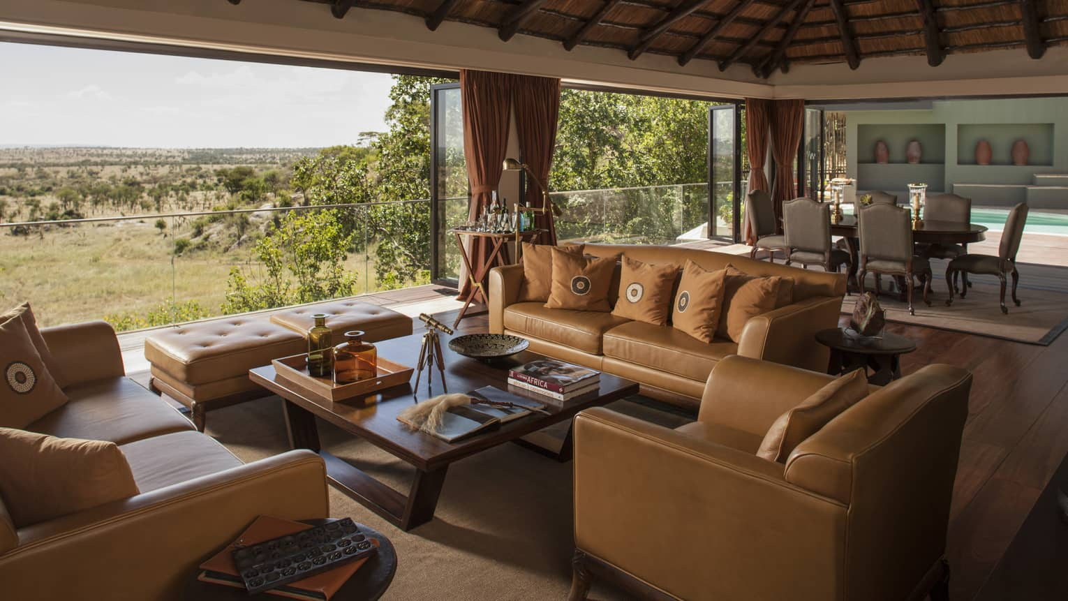Presidential Villa tan leather sofas, chairs around table, large dining room, open wall