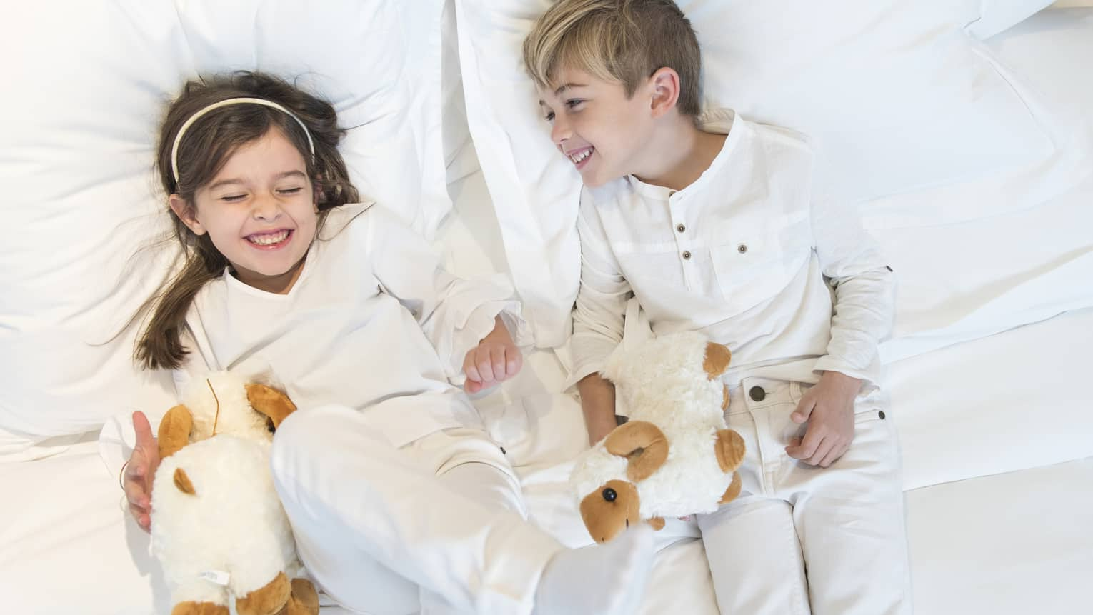 Aerial view of two children wearing white pyjamas with white stuffed animals lying on bed, laughing