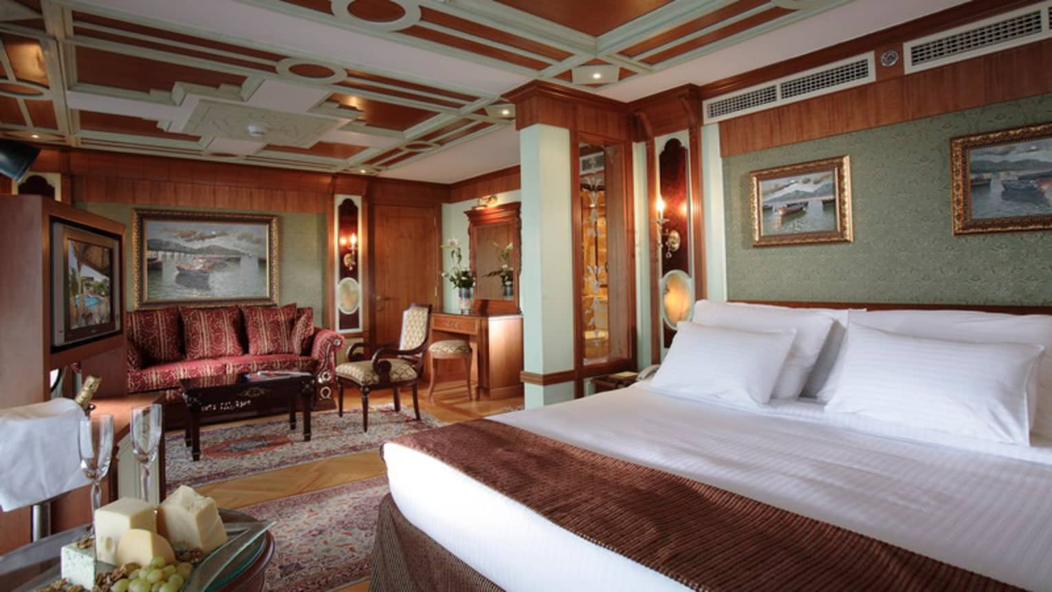 Royal Suite bedroom, wood-panelled walls, paintings with gold frames, red sofa