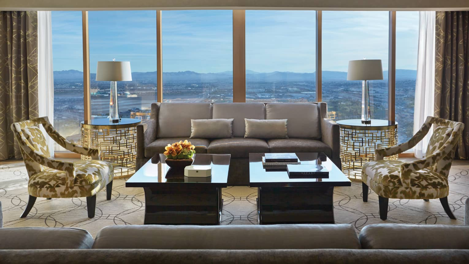Valley-View Suite silver sofas, gold accent chairs, wall of windows with sweeping Las Vegas views