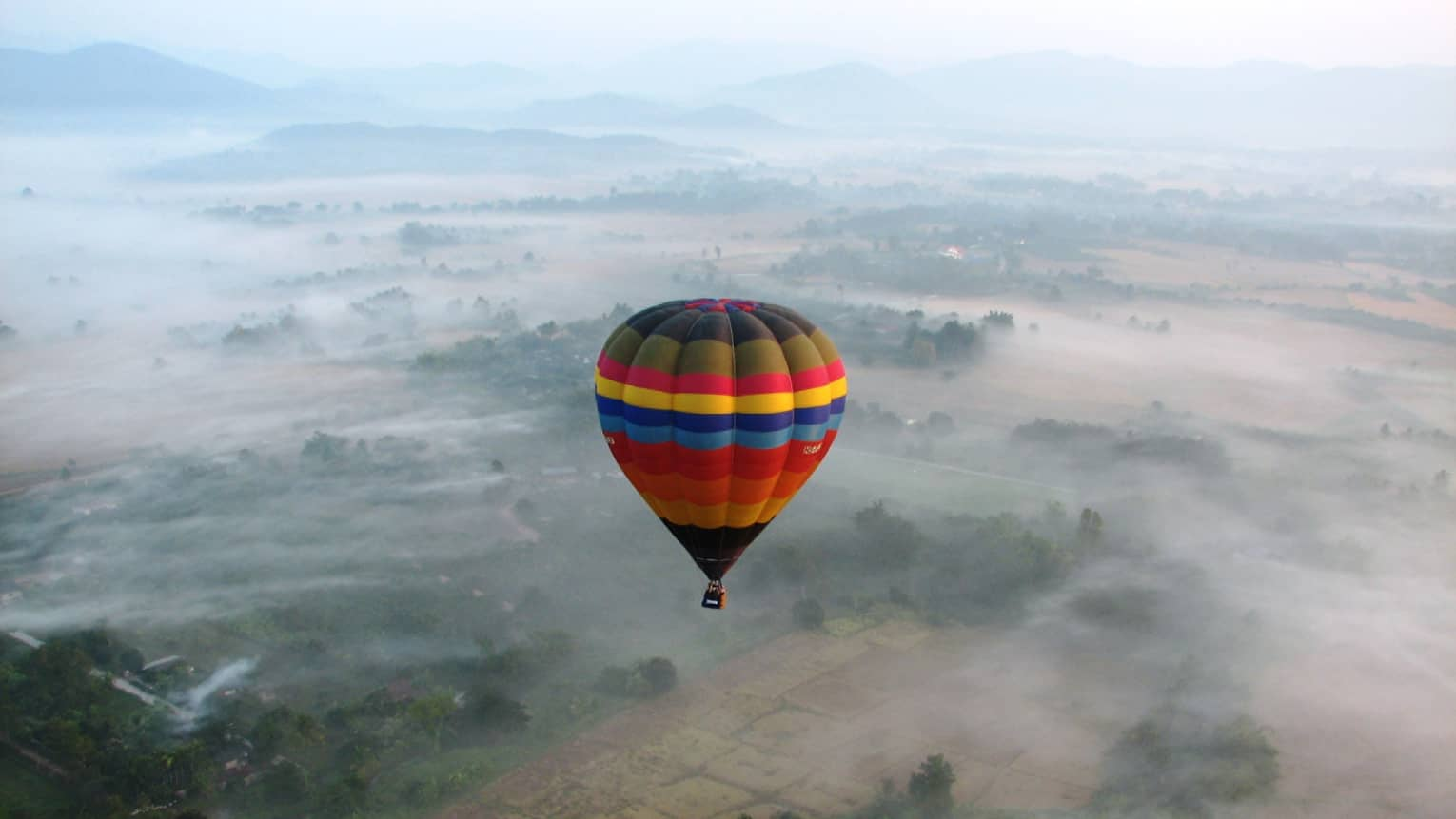 Colourful striped hot air balloon hovers high above field in clouds