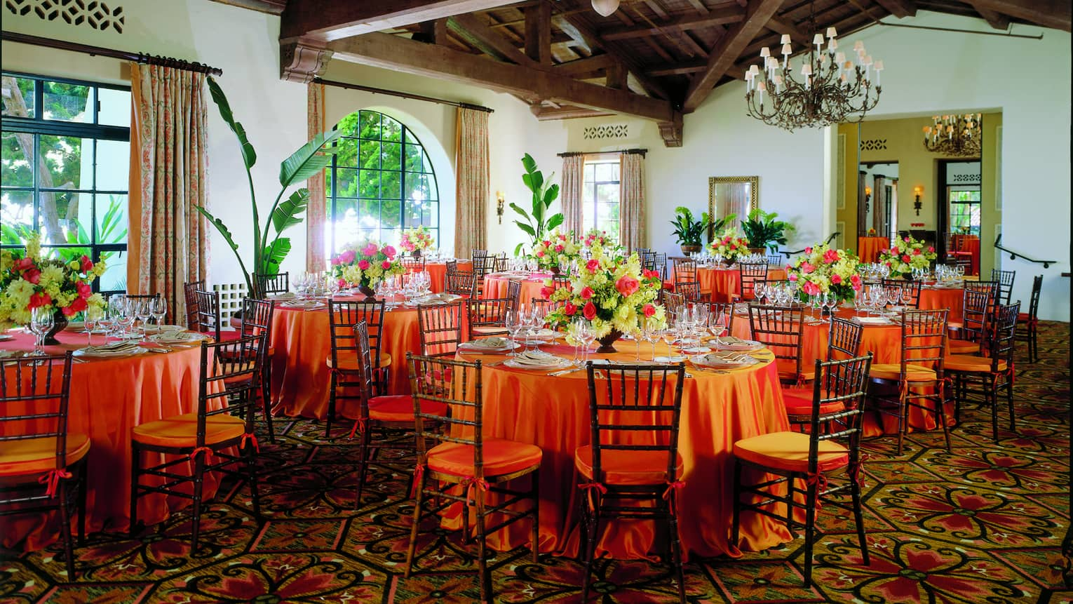 La Marina banquet tables under wood beam ceilings, sunny arched windows and tropical plants