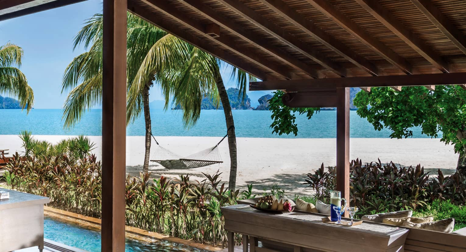 Villa awning over console table with fruit, drinks, plunge pool, by beach
