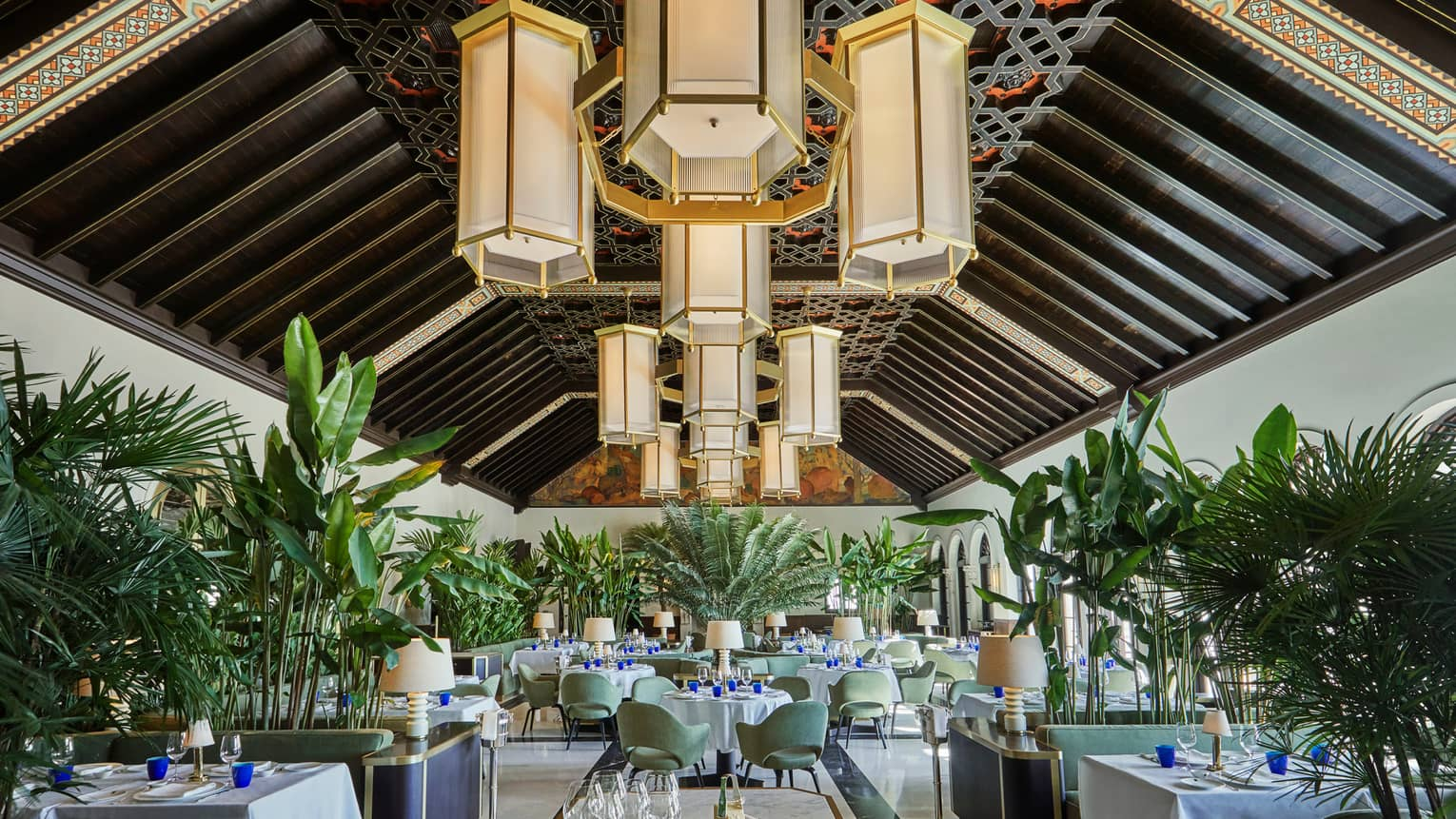 Historic Peacock Alley restored dining room with high ceilings, art deco-style chandeliers and tropical plants
