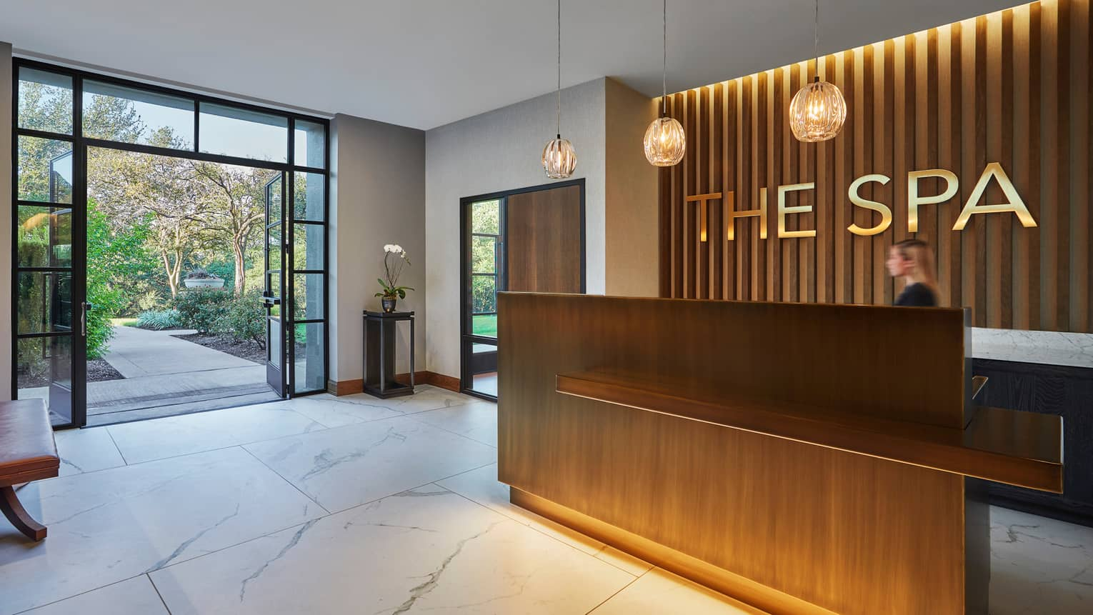 The Spa modern wood reception desk with gold sign, white marble floors, glass door