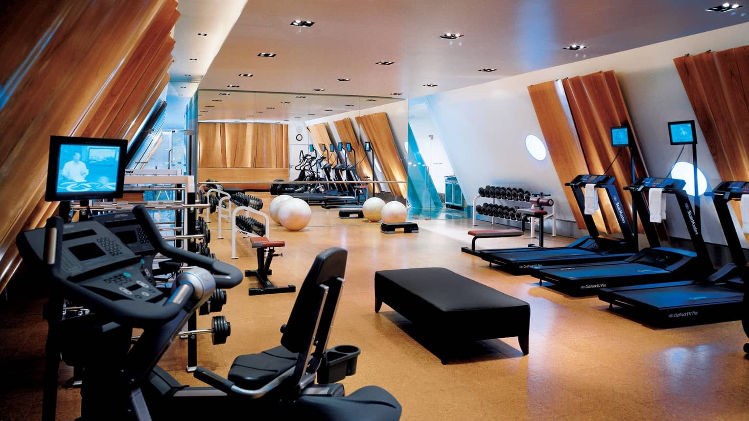 Fitness Centre cardio machines, equipment under sloped ceilings with wood panels