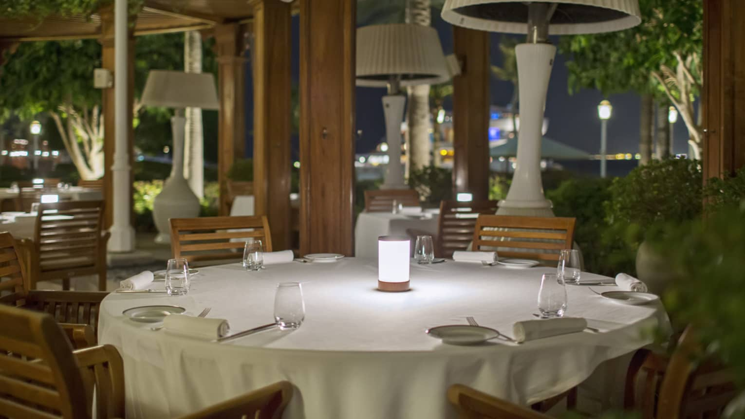 Round formal dining table at Il Tiatro restaurant at night, tall white lamps