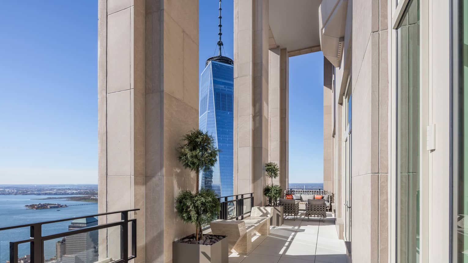 Private penthouse terrace with bench, seating area under soaring stone pillars, Hudson River views