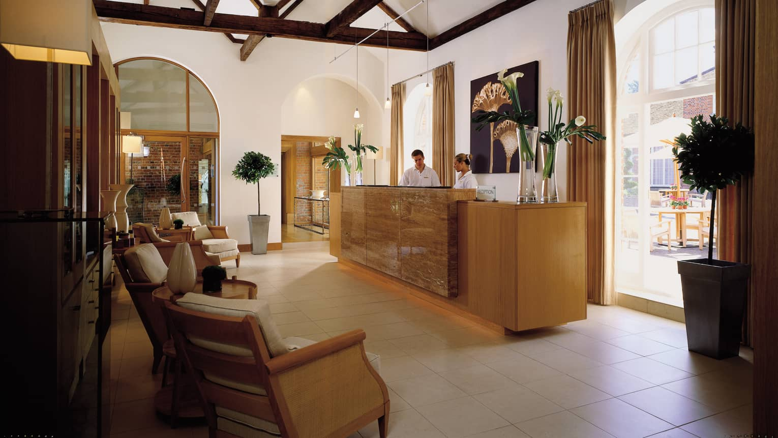 Staff at Spa reception desk under wood beam ceiling, tall bright windows