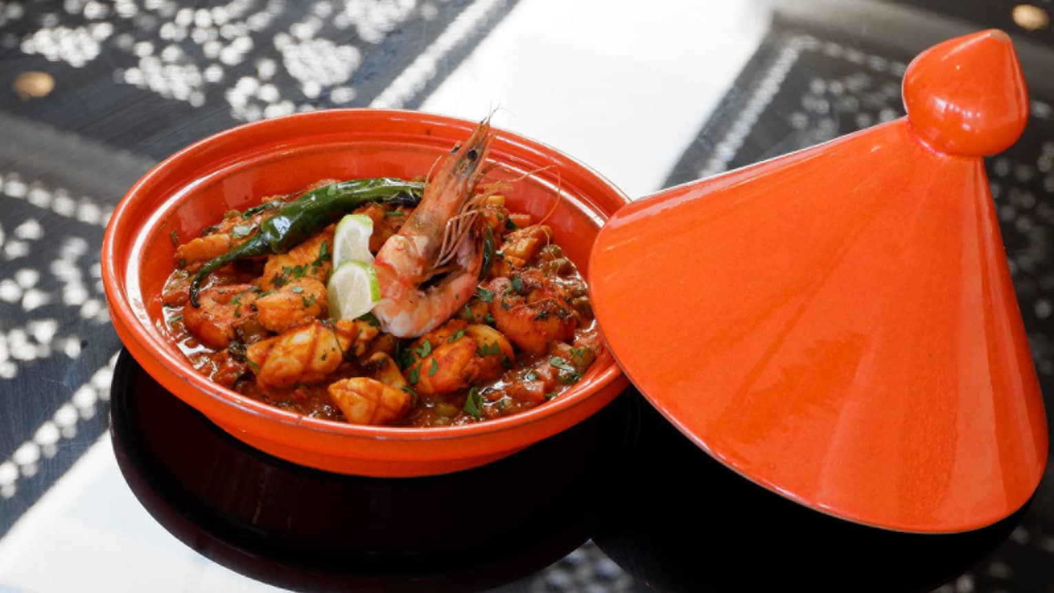 Seafood Tagine fresh fish, prawns in red sauce with lime wedge garnish in red tagine