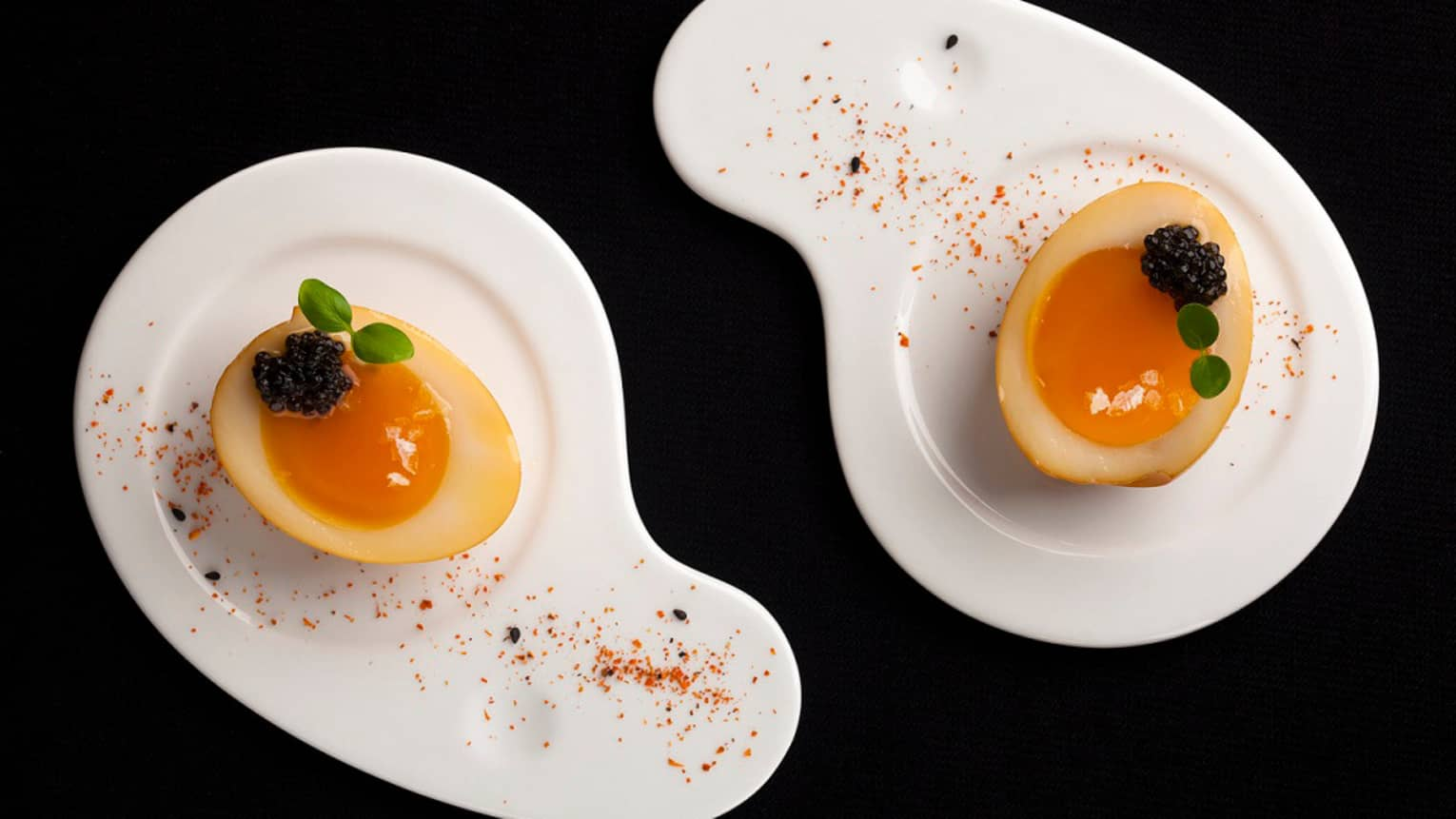 Two tea-smoked eggs with blackberry garnish on curved white plates