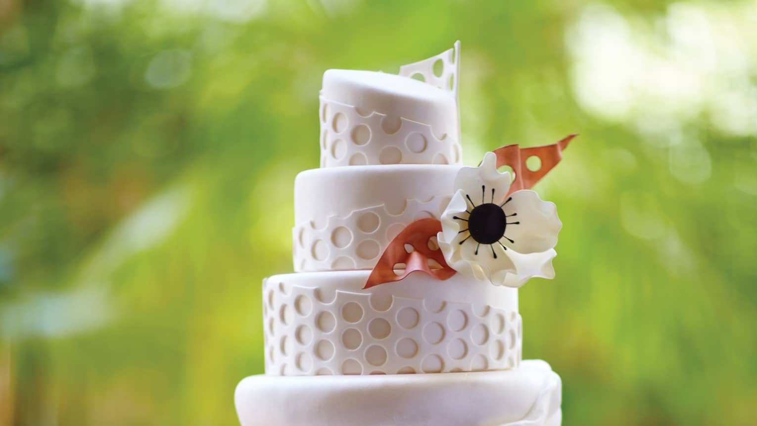 Small four tiered wedding cake decorated with fondant pattern, flower