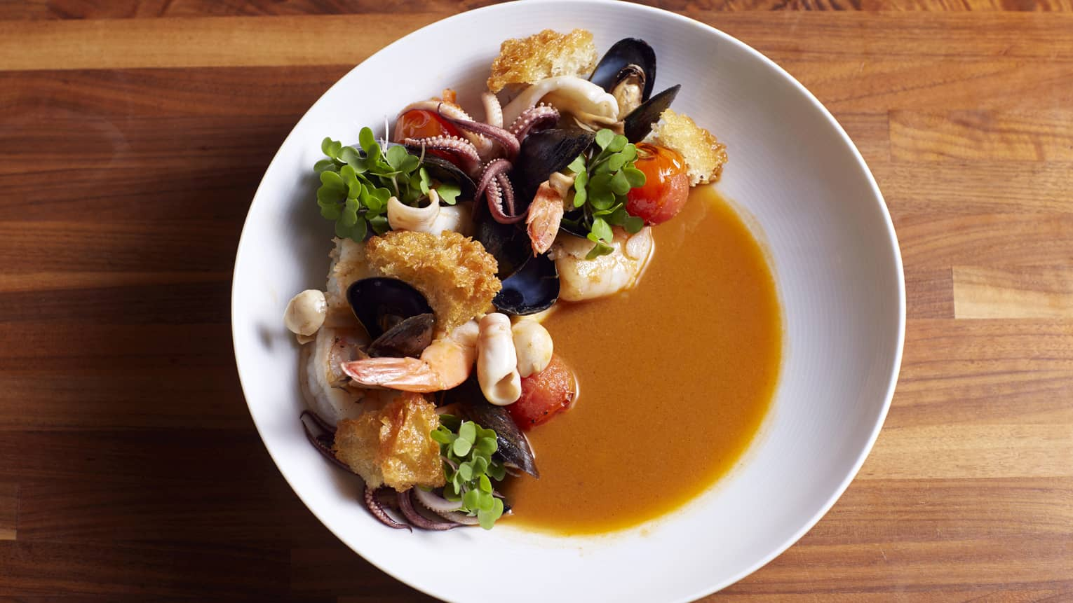 Aerial view of white dish with mixed seafood prawns, mussels, clams, scallops and calamari in red broth