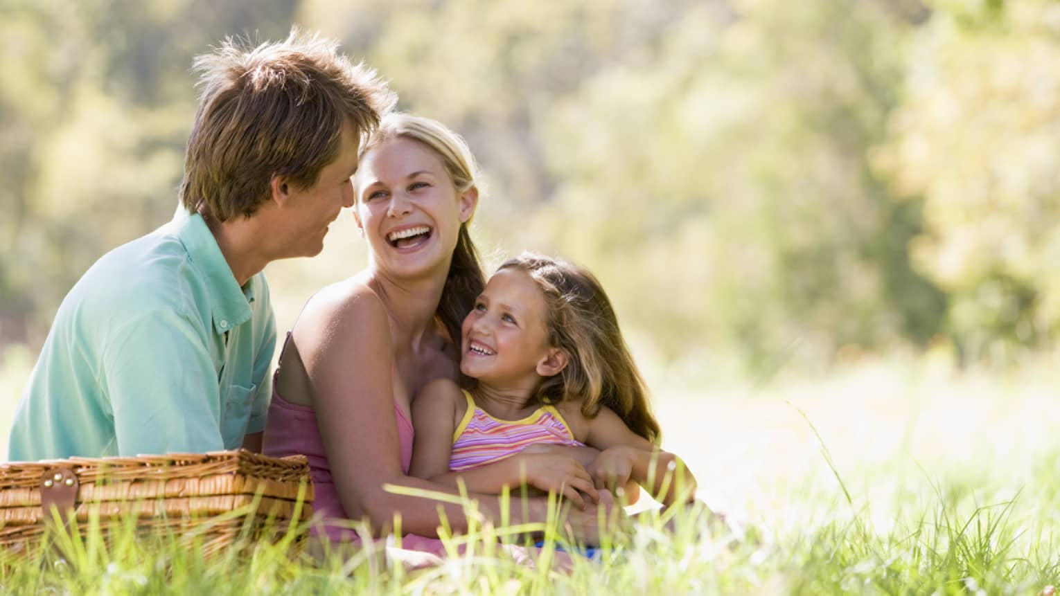 Smiling man, woman and young girl sit in tall grass by picnic basket on sunny day