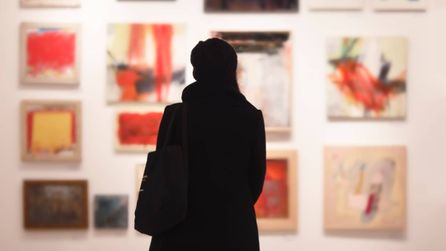 Silhouette of back of woman with hat bag looking at gallery wall with colourful art
