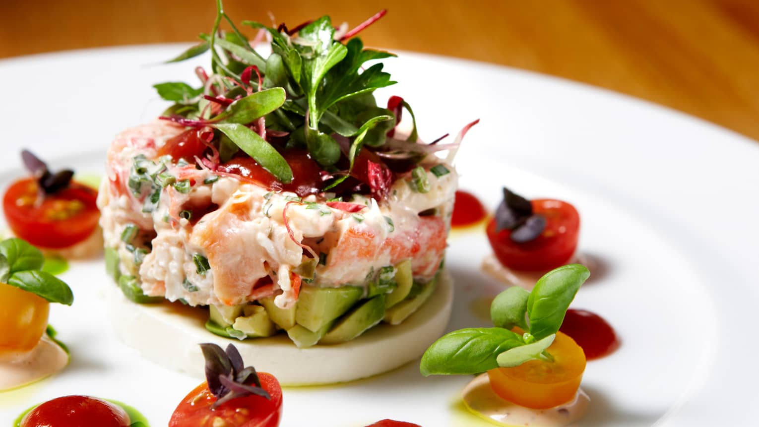 Round Dungeness Crab with chopped avocado, greens garnished with tomatoes, basil