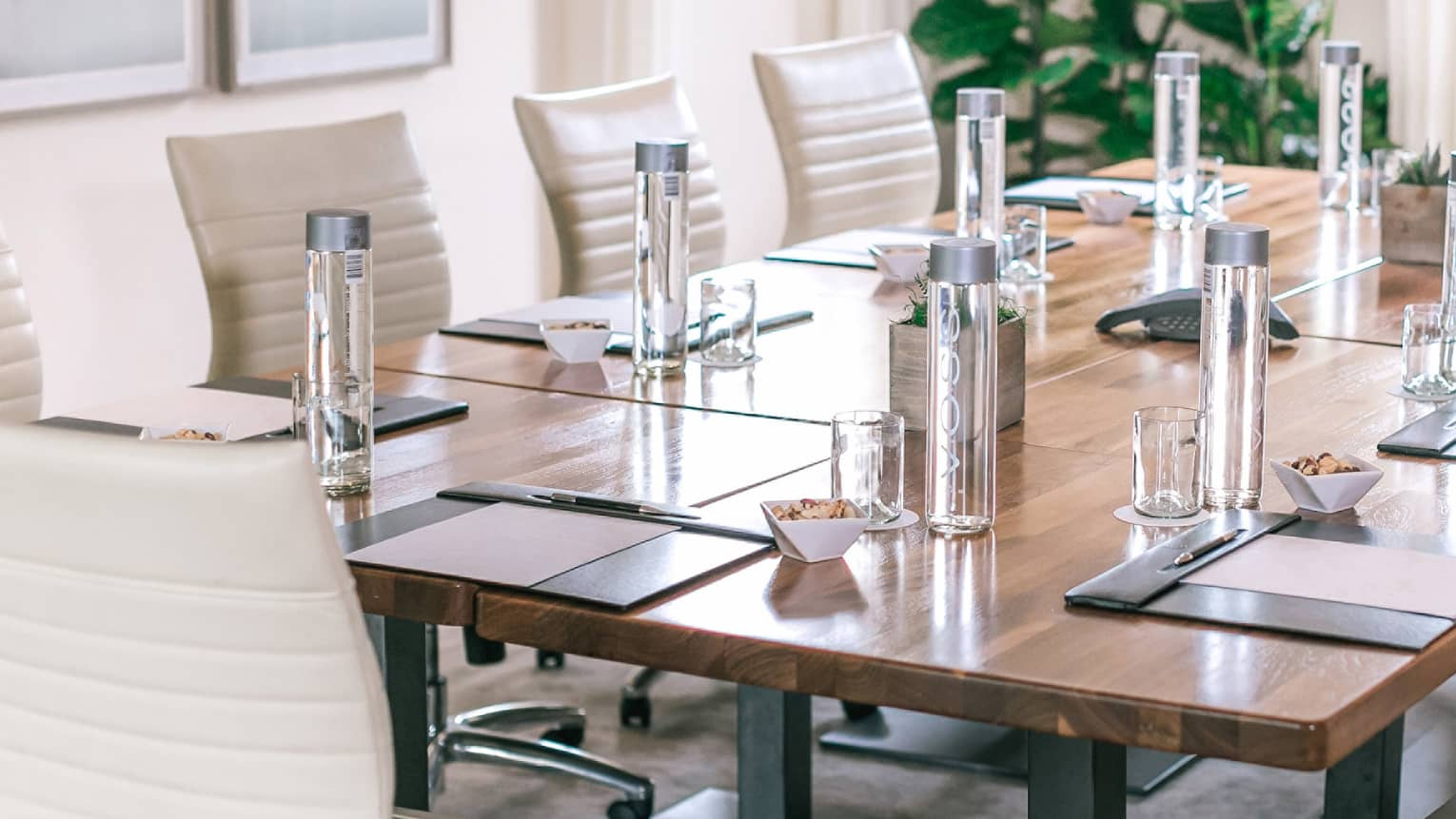 A rectangular boardroom table set with clear glass water bottles and black folders in a naturally-lit room