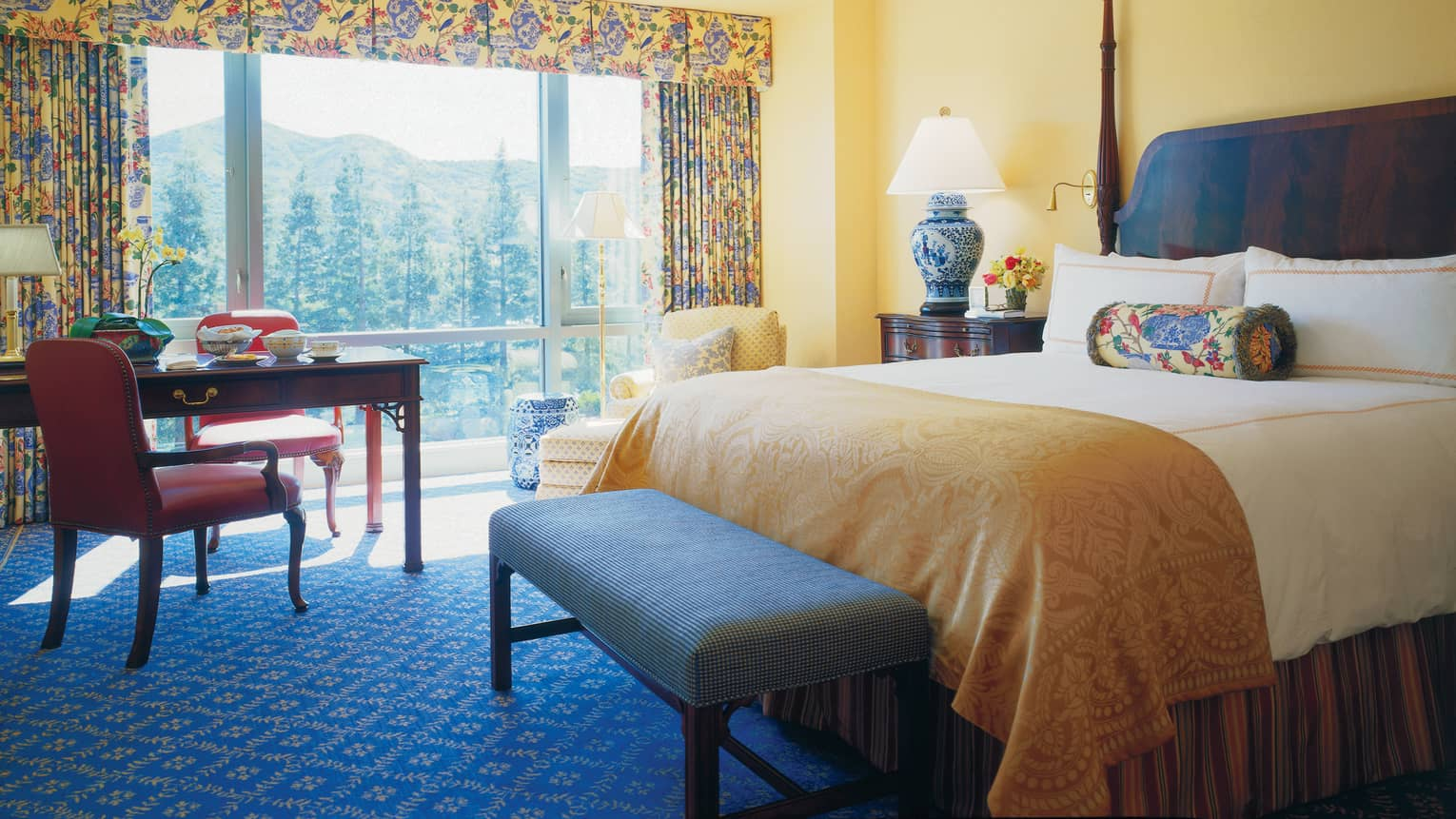 Deluxe Room hotel bed with gold blanket, bench, desk, windows with bright curtains