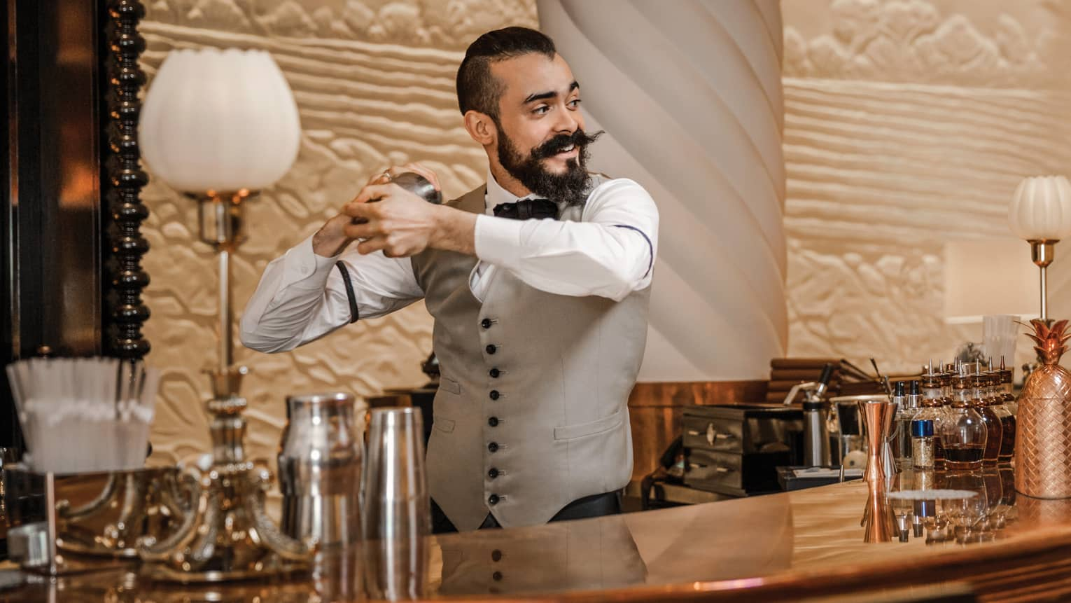 Mixologist with beard and waxed mustache, vest shakes cocktail behind bar