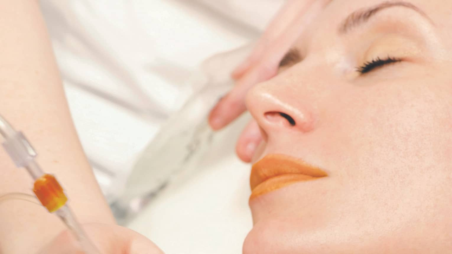Close-up of woman lying on spa table with eyes closed as staff holds facial tool