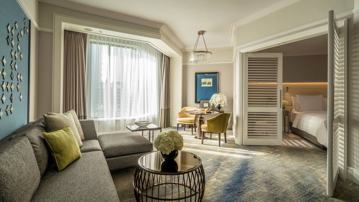 Four Seasons Executive Suite L-shaped sofa by sunny window with white curtains, table, wood shutters