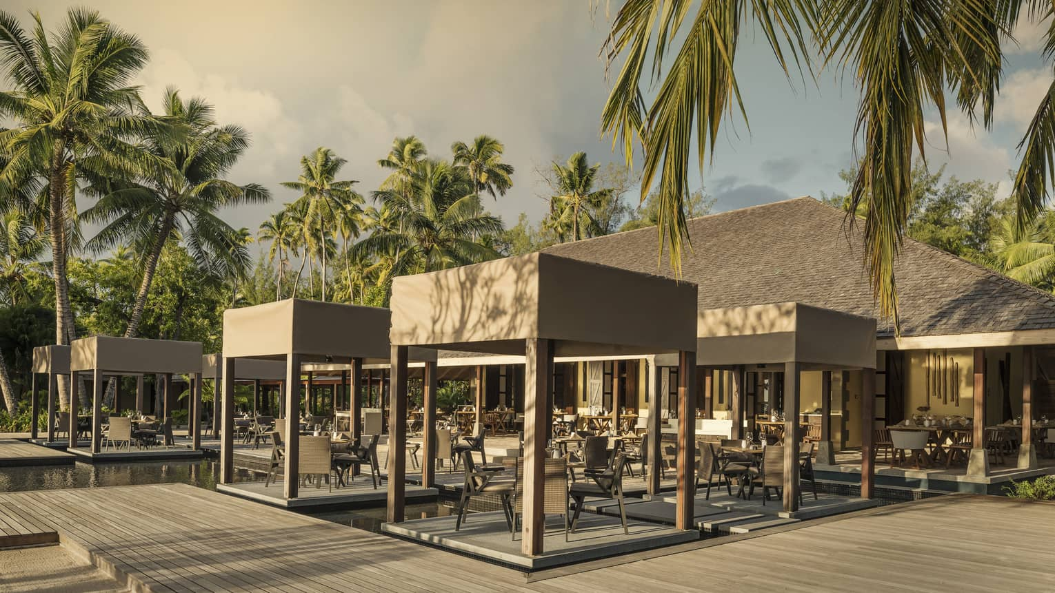 Outdoor Claudine restaurant with tables on decks over water, covered with wooden canopy