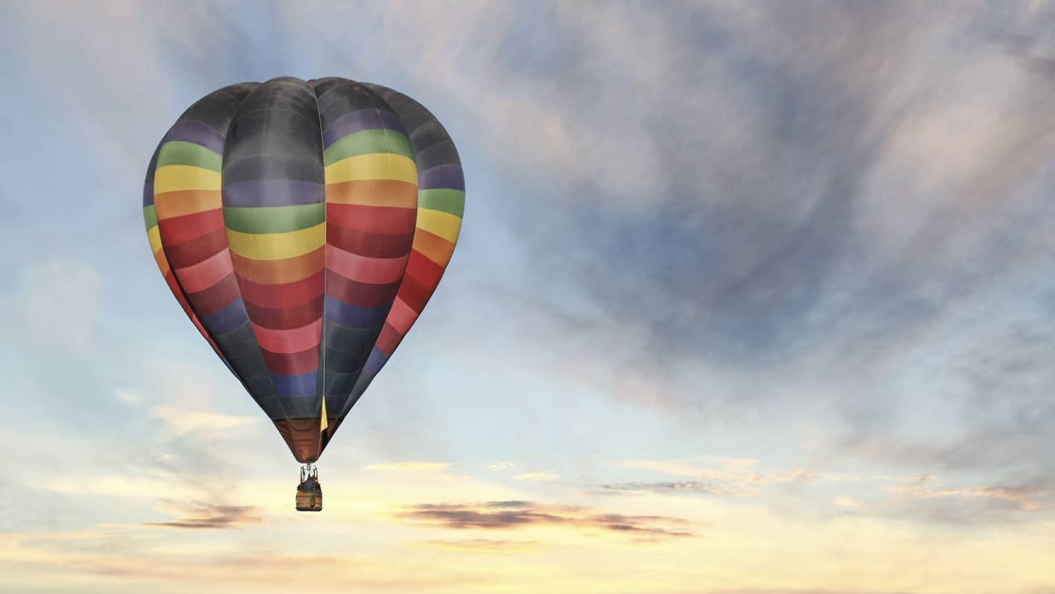 Rainbow-striped hot air balloon floats in the sky at sunset