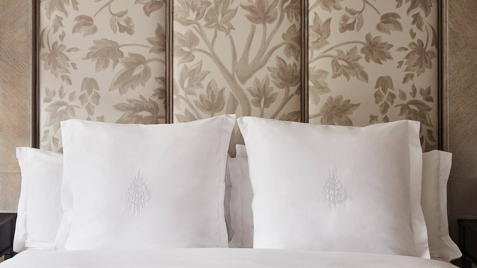 A queen-sized bed with white Four Seasons pillows and a ceiling-height floral upholstered headboard