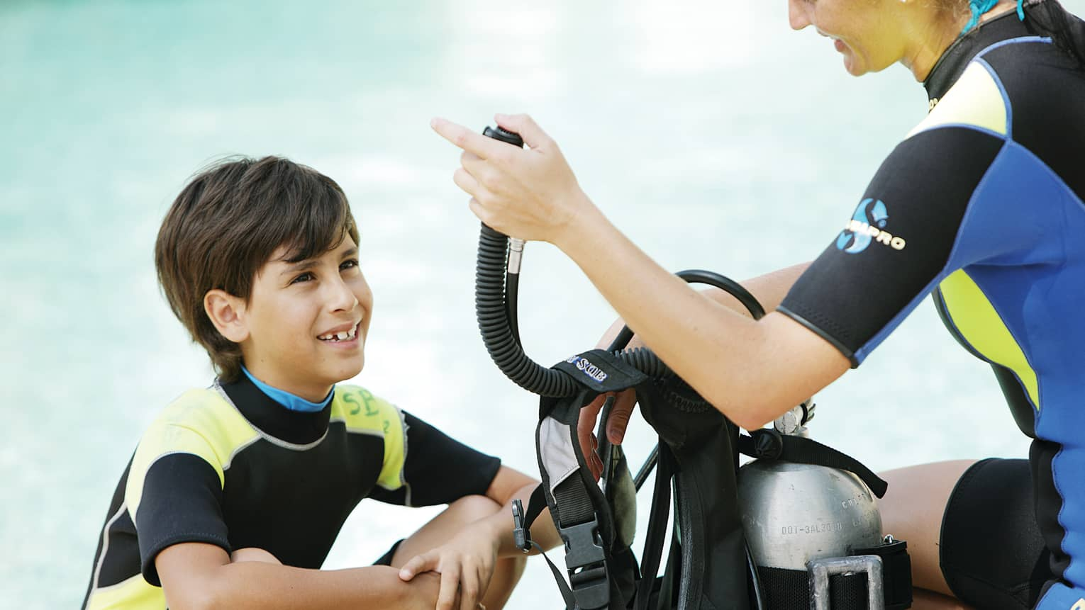 Boy in wetsuit in front of woman giving scuba diving instruction