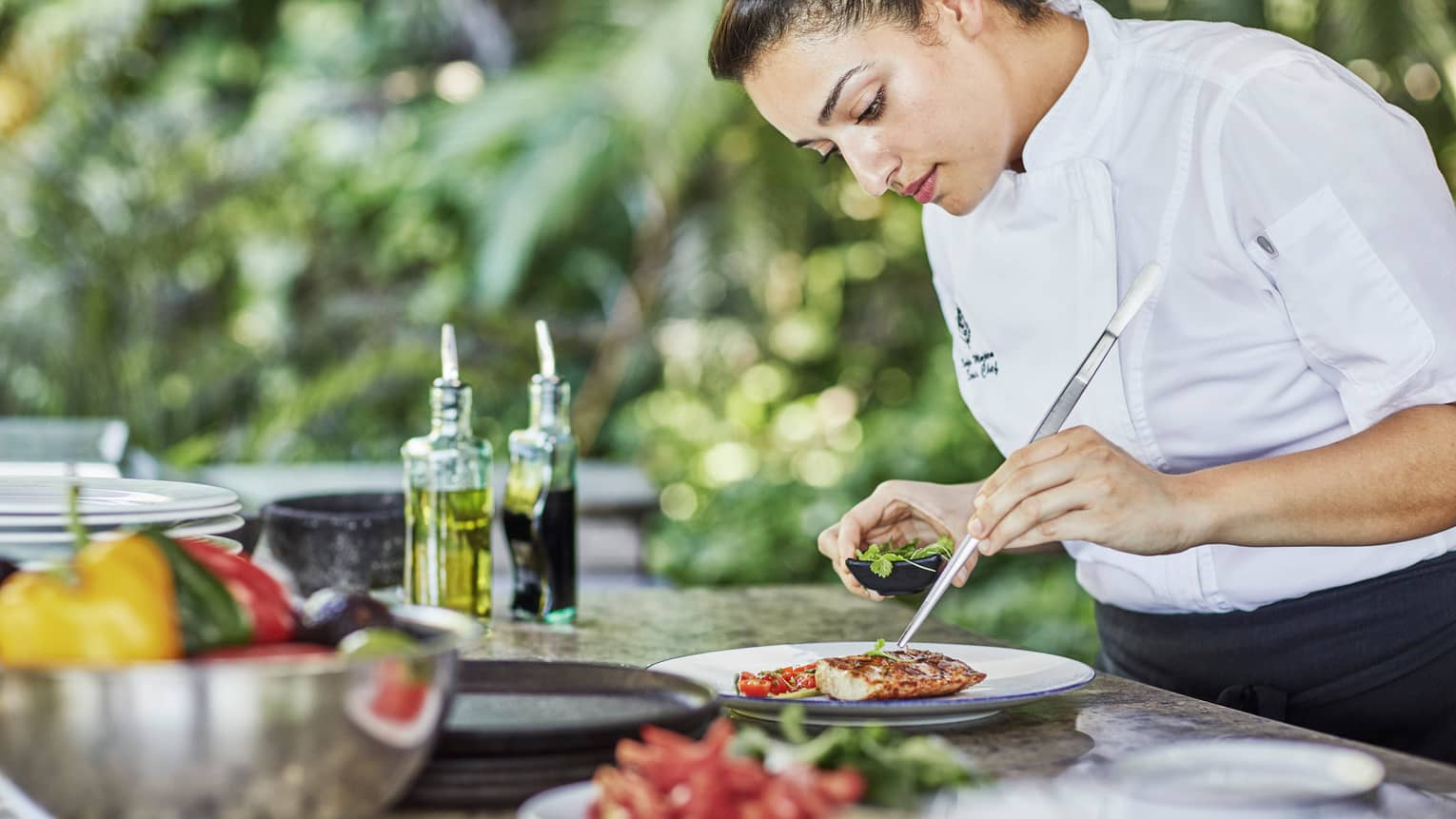 Chef with large tweezers garnishes entree with fresh herbs at outdoor kitchen counter