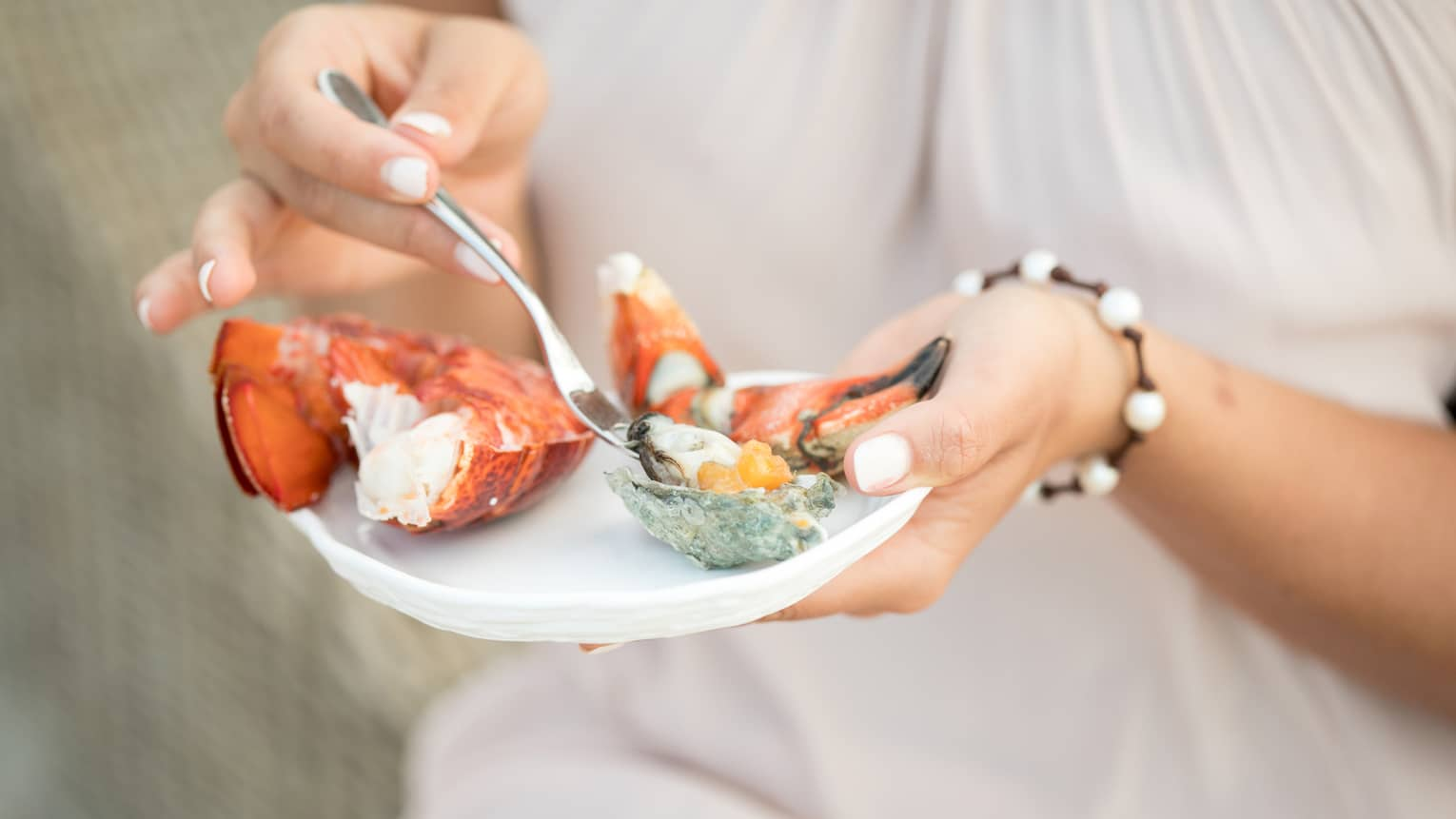 Close-up of woman holding small plate with fresh seafood, digging fork into oyster