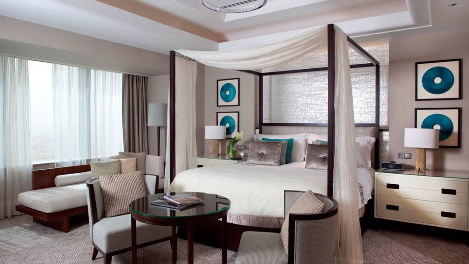 Royal Suite with canopy bed draped with white curtains, round table and chairs, white chaise