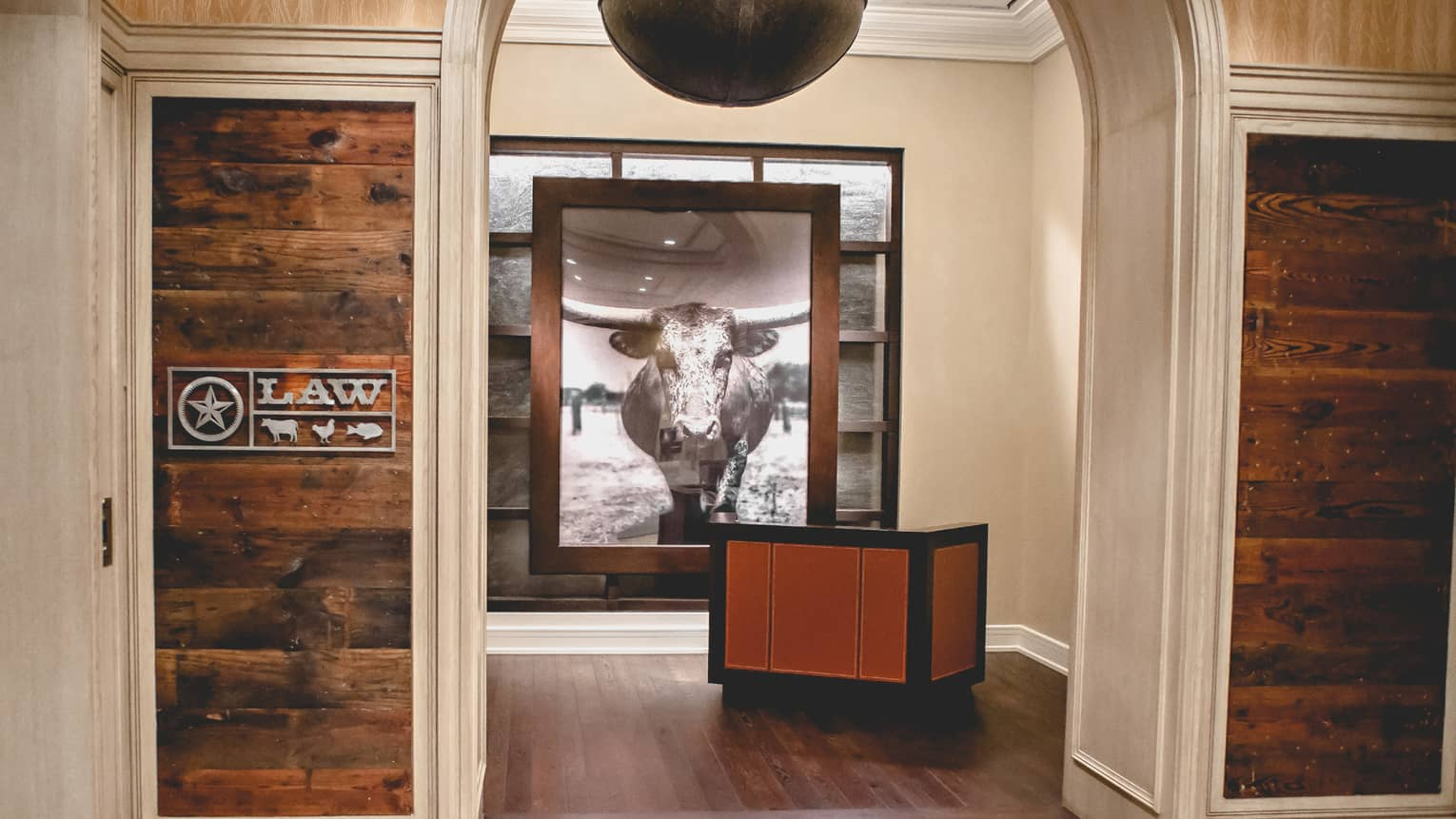 Law restaurant sign, rustic wood reception desk in front of large black-and-white photo of bull