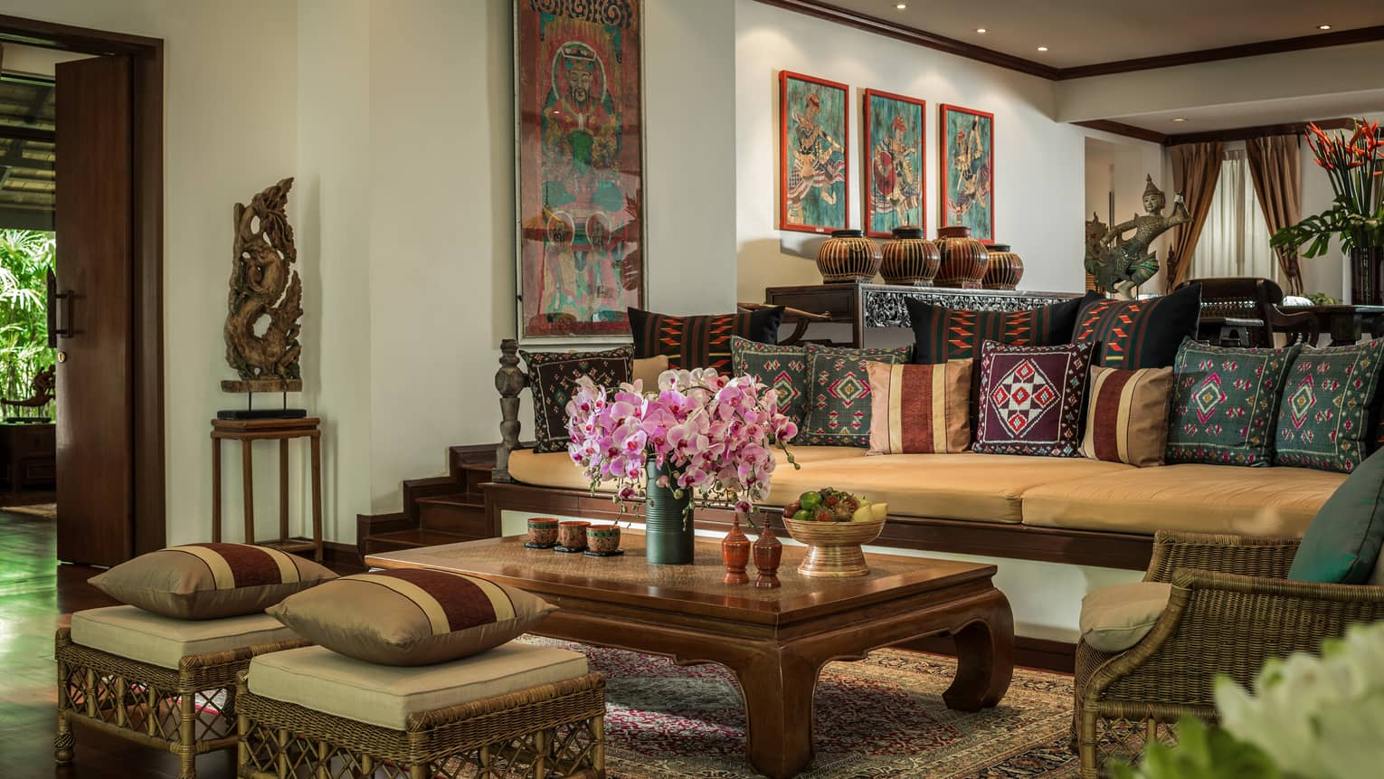 Residence living room with long sofa and two ottomans covered with Thailand textile pillows, wood table