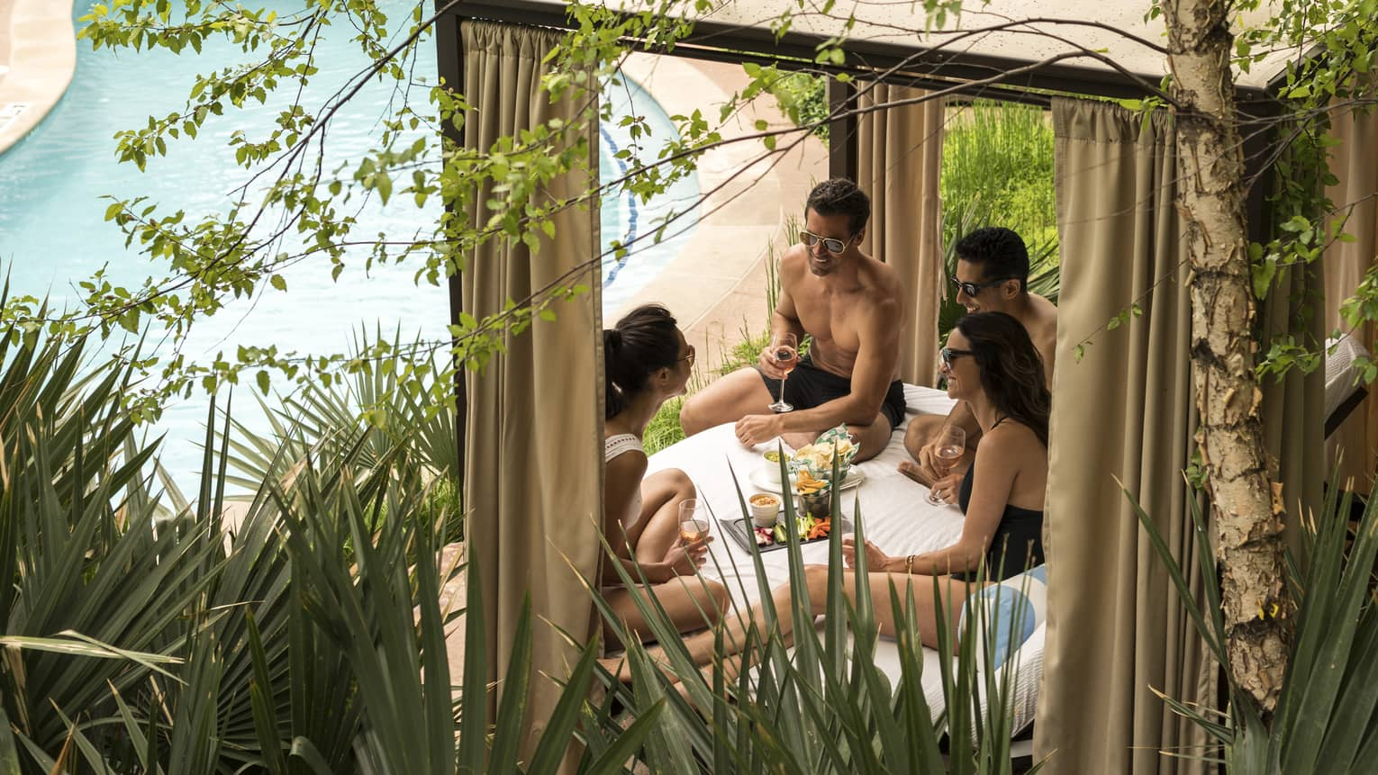 Two men and two women sitting under a cabana and talking next to a pool, there is greenery around them.