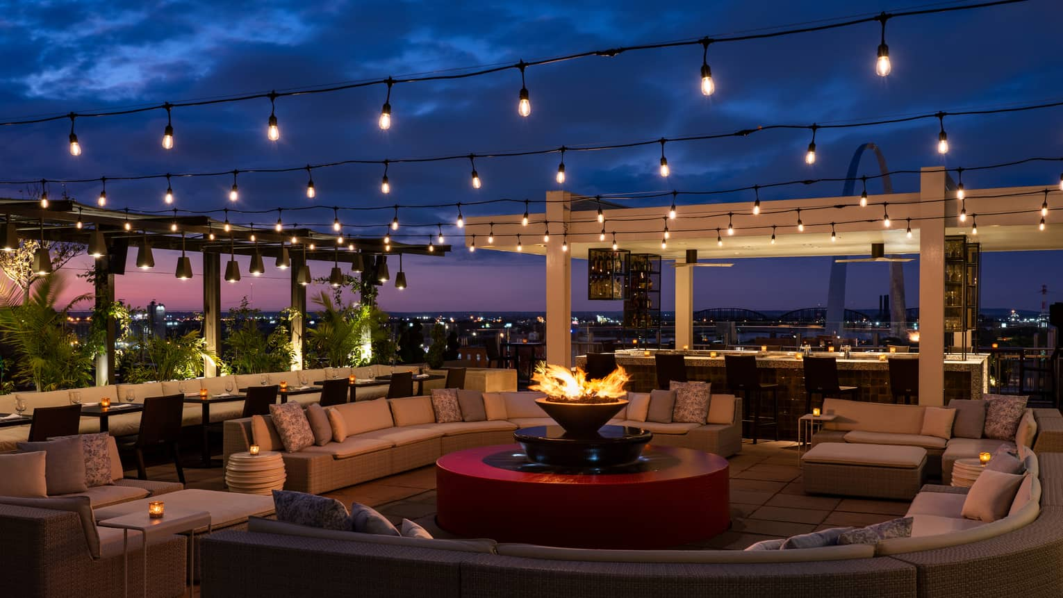The sky is dark beyond the Cinderhouse Rooftop Bar - decorated with a fire pit, curved sectional, rows of hanging lights and shrubbery